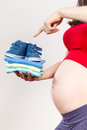 Pregnant woman showing clothing for newborn, expecting for baby Royalty Free Stock Photo