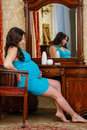 Pregnant woman sits before dressing table young in the room Stock Image
