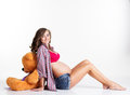Pregnant woman is sitting with big teddy bear in Royalty Free Stock Photo