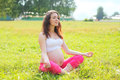 Pregnant woman sitting on grass doing yoga exercise in summer Royalty Free Stock Photo