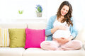 Pregnant woman sitting on a sofa and caressing her belly Stock Image