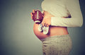 Pregnant woman with small shoes for unborn baby on belly Royalty Free Stock Photo
