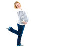 Pregnant woman smiling and holding her belly blond in blue jeans stripped sweater with one leg lifted up isolated on white Stock Images