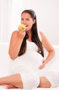 Pregnant woman on sofa eating an apple Royalty Free Stock Images