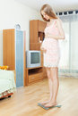 Pregnant woman standing on bathroom scales at home interior Stock Photos