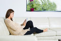 Pregnant woman surfing the net on couch Royalty Free Stock Image