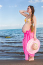 Pregnant woman in swimsuit relaxing at beach Stock Images
