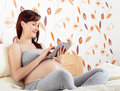 Pregnant woman with tablet sitting in bed and looking someting on Royalty Free Stock Photo