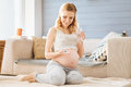 Pregnant woman taking pills in bedroom