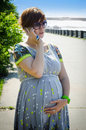 Pregnant woman talking on the phone her Royalty Free Stock Photos
