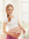 Pregnant woman with tape measuring her belly Royalty Free Stock Photo