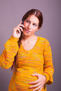 Pregnant woman using cell phone portrait of Stock Photo