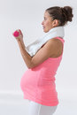 Pregnant woman using handweights happy lifting dumbbells in fitness studio Royalty Free Stock Photography
