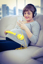 Pregnant woman using smartphone while listening to music at home Royalty Free Stock Image