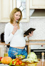 Pregnant woman using a tablet computer to cook in her kitchen Stock Photos