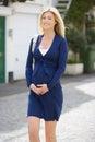 Pregnant Woman Walking Along Urban Sidewalk Royalty Free Stock Photo