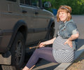 Pregnant Woman with Wheel Brace near Car Stock Images