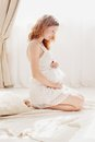 Pregnant woman in white clothes in the bedroom interioP Royalty Free Stock Photo