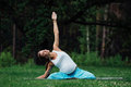Pregnant yoga in the lotus position on the forest background. in the park the grass mat, outdoor, health woman. Royalty Free Stock Photo