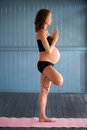 Pregnant yoga super fit young woman balancing whilst doing the tree pose vrikshasana in Stock Photo