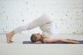 Pregnant young woman doing prenatal yoga. Plow pose