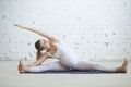 Pregnant young woman doing prenatal yoga. Side bend in seated sp Royalty Free Stock Photo