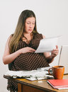 Pregnant young woman paying bills at laptop computer mother to be reads and bank statements while seated a desk with stacks of Royalty Free Stock Photos