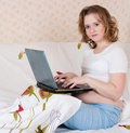 Pregnant young woman using a laptop Stock Images