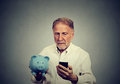 Preoccupied man looking at his mobile phone holding piggy bank Royalty Free Stock Photo