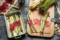 Preparation baked asparagus with prosciutto ham on old wooden table Royalty Free Stock Images