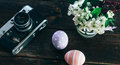Preparation for Easter. Colorful handmade Easter eggs, paint, retro camera and vase with flowers on a wooden background