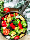 Preparation garnish. Raw fresh vegetables - broccoli, eggplant, bell peppers, tomatoes, onions, garlic in a cast iron frying pan Royalty Free Stock Photo