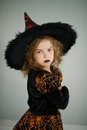 Preparation for Halloween. Beautiful girl 8-9 years shows the evil witch.
