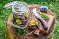Preparation for pickled plums in summer on old wooden stump Stock Photos