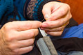 Preparation for sewing male hands give thread the needle Royalty Free Stock Photo