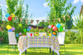 Prepared birthday table in summer green garden Royalty Free Stock Photo