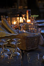 Prepared table for a rustic outdoor dinner at night with wineglasses bread and candles vertical Royalty Free Stock Images