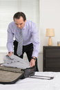 Preparing for a business trip mature businessman packing his cl clothes to suitcase Royalty Free Stock Photos