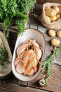Preparing chicken for cooking with spices and vegetables on old wooden table Stock Photo