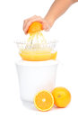 Preparing fresh orange juice squeezed with electric juicer on a white background Stock Image