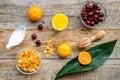 Preparing healthy summer breakfast. Muesli, milk, oranges, cherry, on wooden table background top view