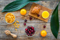 Preparing healthy summer breakfast. Muesli, oranges, cherry, juice on wooden table background top view