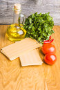 Preparing italian lasagna  with fresh  red  tomatoes and mint on sheets of dried pasta Royalty Free Stock Photo