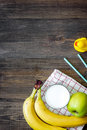 Preparing quick lunch for schoolchild. Fruits on dark wooden table background top view copyspace