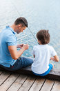 Preparing rod for fishing rear view of father and son sitting at the quayside and Royalty Free Stock Photos