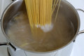 Preparing spaghetti pasta meal cooking noodles in water pot Royalty Free Stock Photography