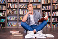 Preparing to his final exams thoughtful young man holding note pad and touching chin with pen while sitting against bookshelf Royalty Free Stock Photo