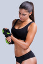Preparing to sports training beautiful young sporty woman with perfect body adjusting her gloves while standing against grey Stock Photography