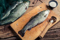 Preparing trout for dinner in the countryside on old wooden table Royalty Free Stock Image