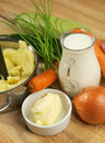 Preparing vegetables puree mashed potato jar of milk butter onion carrot greens and zucchini closeup on wooden background Royalty Free Stock Photography